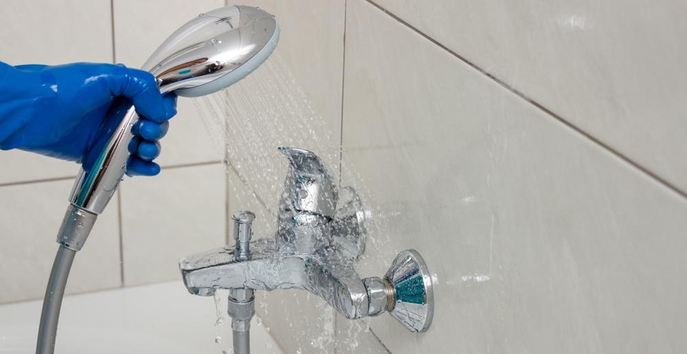 Wie ist die Wirkung von Entkalker? Hand mit Brause spült mit Wasserstrahl die Armatur im Bad